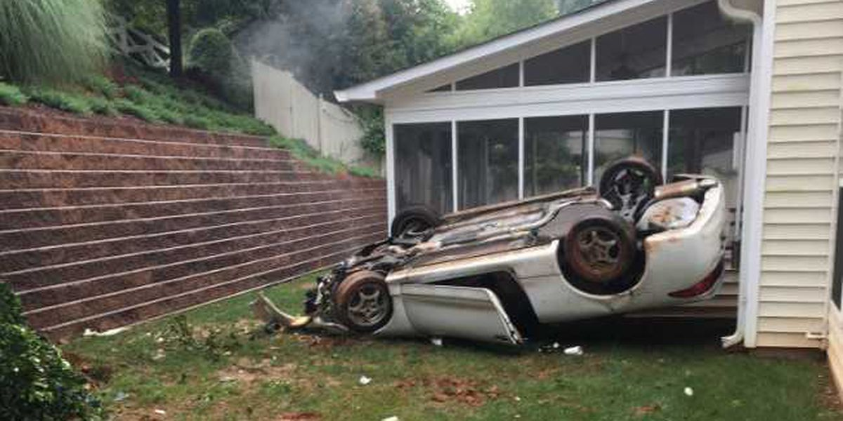Car careens off road, through fence, down 20-foot retention wall, landing in woman's backyard
