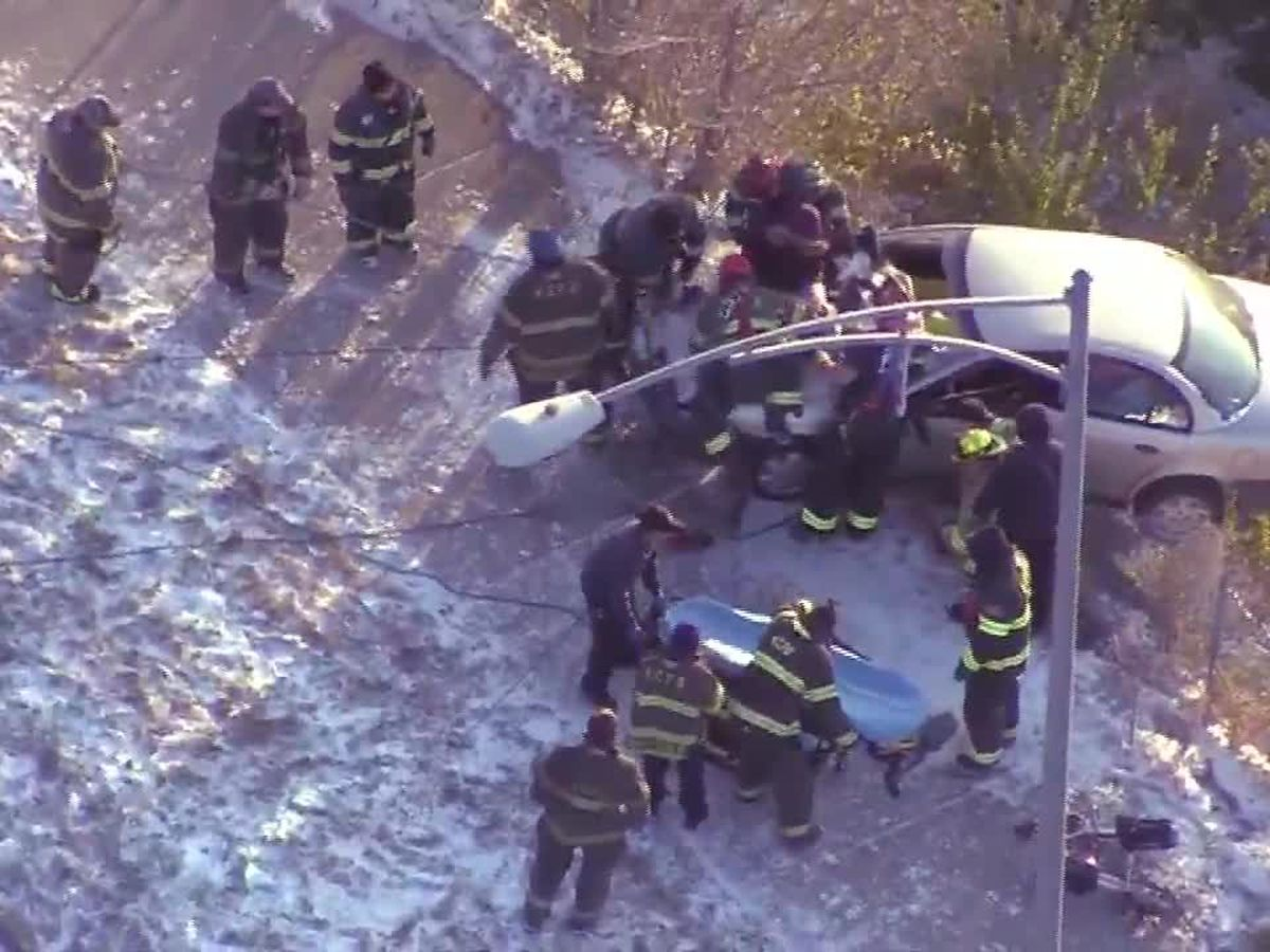 Crews rescue woman from car dangling off the edge of a snowy roadway
