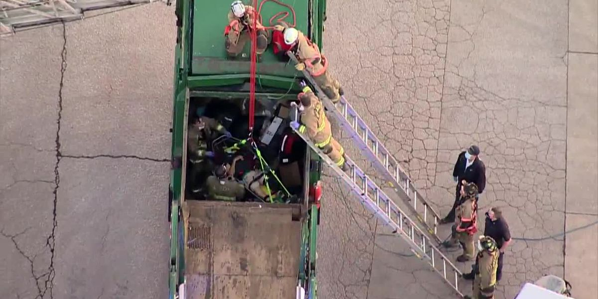 Firefighters rescue man trapped in garbage truck